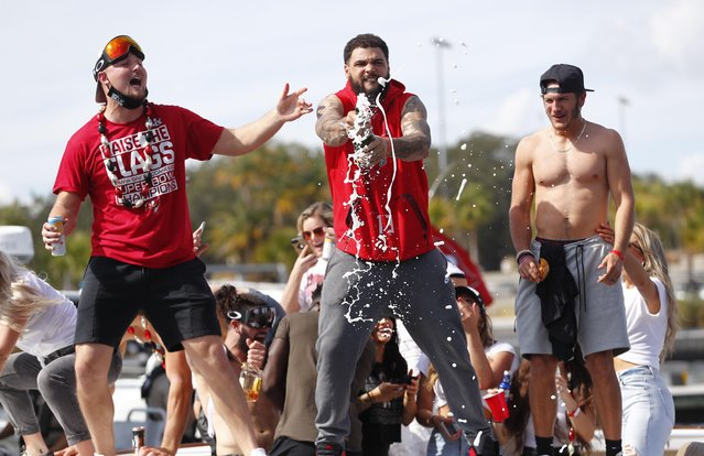 Tampa Bay Buccaneers wide receiver Mike Evans and teammates celebrate with champagne during a boat parade to celebrate victory in Super Bowl LV against the Kansas City Chiefs in Tampa Bay, Florida, February 10, 2021. (Photo by Kim Klement/USA TODAY Sports)