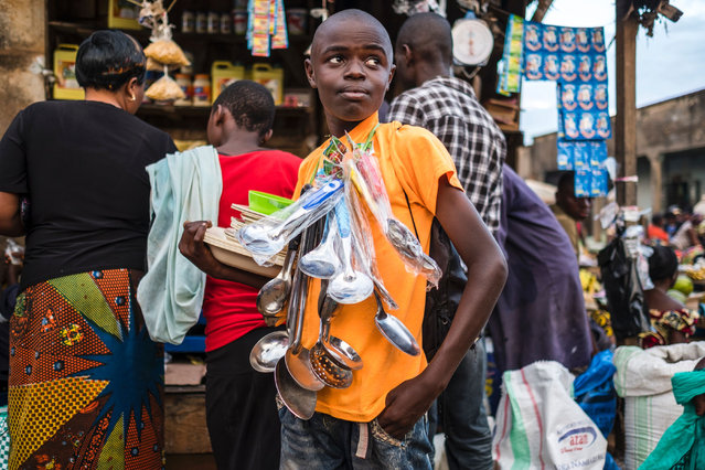 A boy sells kitchen ware at a market in Beni, Democratic Republic of the Congo on November 9, 2016. (Photo by Eduardo Soteras/AFP Photo)