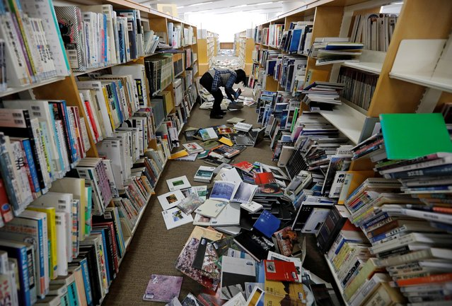 A staff member of a library tries to restore books after they fell from book shelves by a strong earthquake at Iwaki City library in Iwaki, Fukushima prefecture, Japan, February 14, 2021.  The 7.3 magnitude quake struck shortly before midnight Saturday and cracked walls, shattered windows and set off a landslide in Japan's Fukushima, the area closest to the epicenter. (Photo by Issei Kato/Reuters)
