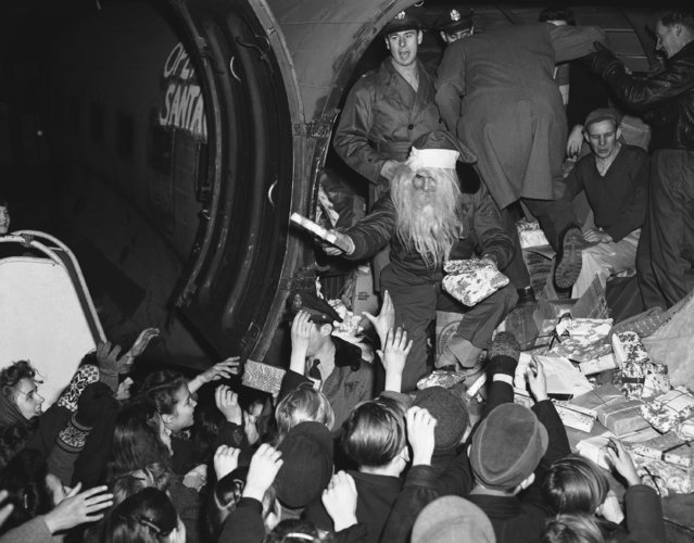 Young Berliners get a treat at the U.S. Army's Tempelhof Airport in Berlin, December 15, 1948. Christmas gifts from a flying Santa, Lt. John Konop of Astoria, NY. This is the first planeload of gifts to be distributed to Berlin children under the Air Forces Christmas program, Operation Santa Claus. The gifts were donated by people in the United States and flown to Berlin via the air lift. (Photo by Henry Burroughs/AP Photo)