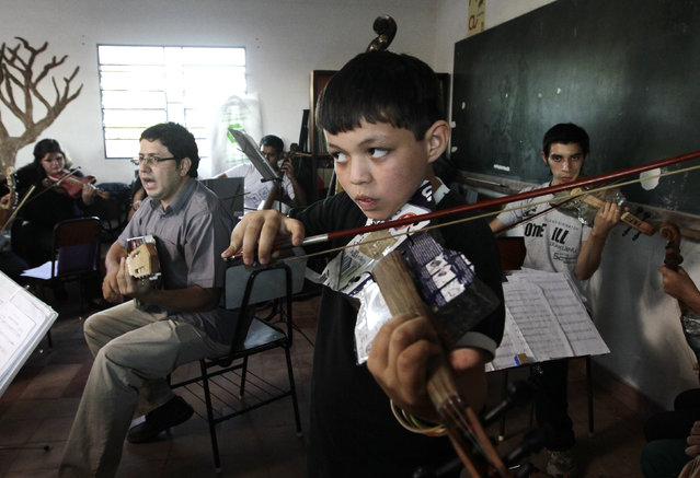 Director of the Orchestra of Recycled Instruments of Cateura, Favio Chavez (L, gray shirt), leads his music students during a rehearsal at the Vy'a Renda education center in Cateura, near Asuncion, May 8, 2013. (Photo by Jorge Adorno/Reuters)
