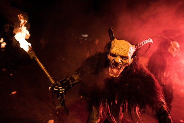 A person dressed as the Krampus performs during the 9th Krampus meeting show in Serfaus, Tyrol, Austria, 12 November 2016. Several thousand people watched the parade of about 27 artists groups from Austria and South Tyrol, Italy. The Krampus is a folklorical figure who, during the Christmas season, punishes children who have misbehaved. (Photo by Christian Bruna/EPA)