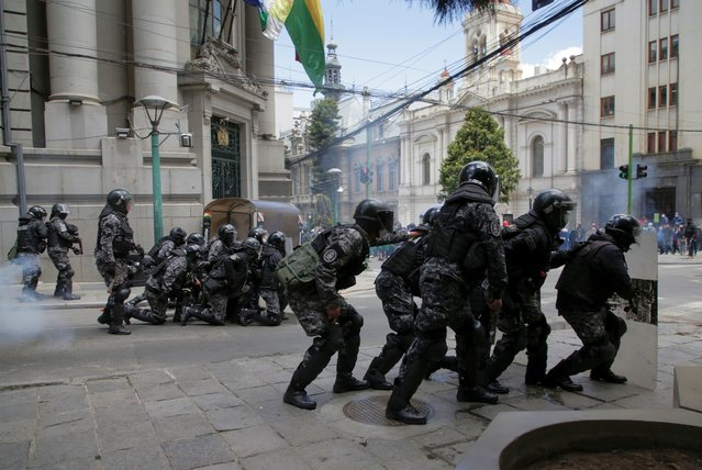 Riot police take position during a protest of healthcare workers against new government measures amidst the coronavirus disease (COVID-19) outbreak, in La Paz, Bolivia, February 23, 2021. Conasa (National Health Council) called for a strike last friday after President Luis Arce passed an emergency law. (Photo by David Mercado/Reuters)