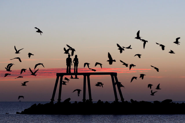"""Birds fly over the statue entitled """"Couple"""" by British artist Sean Henry at dawn in Newbiggin-by-the Sea, Northumberland, Britain on February 26, 2021. (Photo by Lee Smith/Reuters)"""