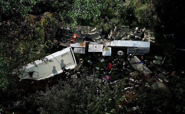 Firefighters work on the wreckage of a bus that plunged off the A16 highway near Avellino in southern Italy, on July 29, 2013. The tour bus filled with Italians returning home after an excursion plunged off the highway into a ravine Sunday night after it smashed into several cars that were slowed by heavy traffic. At least 37 people died in the accident. (Photo by Gregorio Borgia/Associated Press)