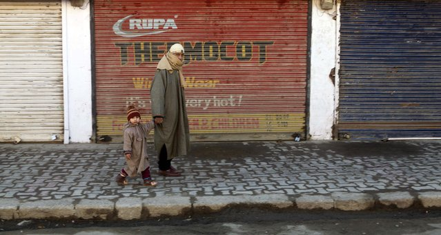 An man walks with a child past closed shops during a general strike in Srinagar, India, Monday, January 26, 2015. Shops remained closed Monday on India's Republic Day as separatists called for a general strike in the Indian-controlled portion of the disputed Kashmir region. (Photo by Dar Yasin/AP Photo)