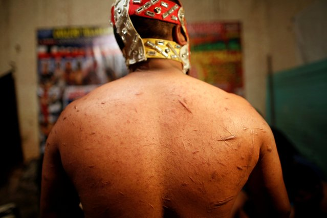 A wrestler shows the scars on his back backstage at a temporary wrestling ring inside a car wash in Tulancingo Hidalgo, Mexico October 8, 2016. (Photo by Carlos Jasso/Reuters)