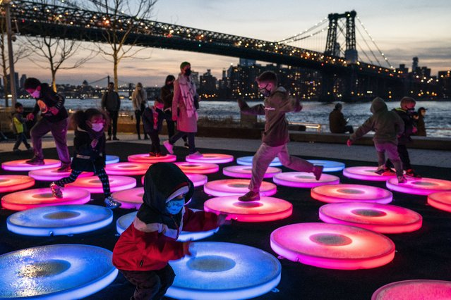 Children play on Reflect, an art installation by artist Jen Lewin in Brooklyn's Domino Park near the base of the Manhattan Bridge, Wednesday, March 10, 2021, in New York. After the virus descended on New York, the only sounds in the streets were wailing ambulance sirens. A year after the pandemic began, the nation's largest metropolis – with a lifeblood based on round-the-clock hustle and bustle, push and pull – is adapting and showing new life. (Photo by John Minchillo/AP Photo)