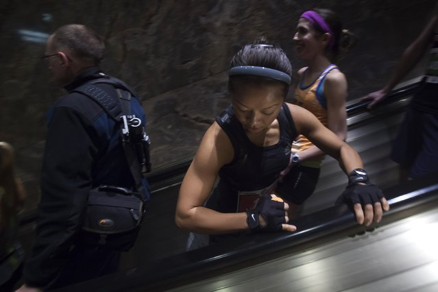 A member of the Women's Elite class flexes har arm as she rides down an escalator before the start of the 38th Annual Empire State Building Run-Up in the Manhattan borough of New York February 4, 2015. (Photo by Carlo Allegri/Reuters)