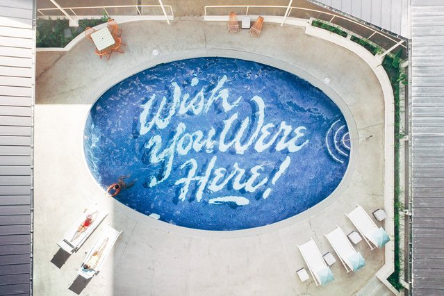 "World's Greatest Swimming Pools: Surfjack Hotel Oahu, Hawaii. Since a well-cropped social media post can serve as a modern-day postcard, The Surfjack has you covered with a jovial ""Wish You Were Here!"" etched into their pool's base. Painted by Honolulu-based artist Matt Tapia, the eye-catching display serves as the backdrop for poolside events from DJ parties to screenings with the filmmaker present. (From $200). (Photo by The Surfjack Hotel & Swim Club)"