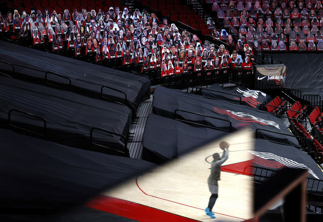 Seen in a plexiglass reflection, Damian Lillard #0 of the Portland Trail Blazers warms up in front of cardboard cutouts of fans before the game against the Brooklyn Nets at Moda Center on March 23, 2021 in Portland, Oregon. (Photo by Steph Chambers/Getty Images)