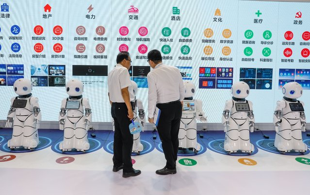 Chinese participants look at robots during the 2018 World Robot conference in Beijing, China, 15 August 2018. (Photo by Roman Pilipey/EPA/EFE/Rex Features/Shutterstock)