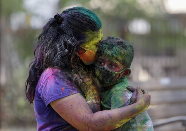 An Indian woman smeared in colors and wearing mask embraces her child during Holi festival celebrations in Mumbai, India, Monday, March 29, 2021. (Photo by Rajanish Kakade/AP Photo)