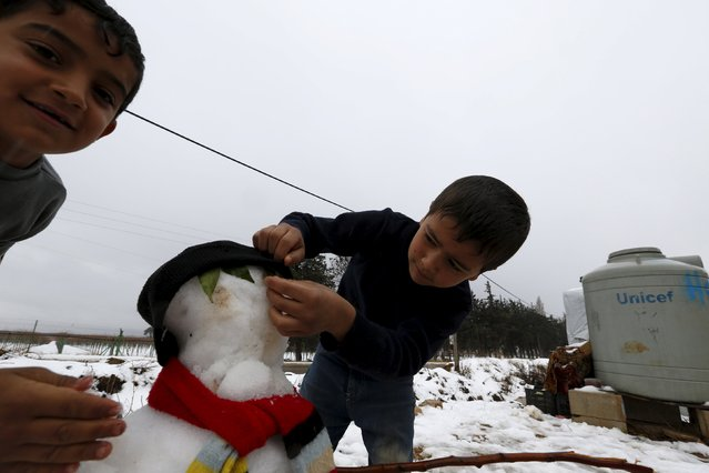 A Syrian child Mohammed (L) and his bother Ali from Raqqa make a snowman in the Bekaa Valley in Lebanon after the first heavy snow storm hit Lebanon, January 3, 2016. (Photo by Jamal Saidi/Reuters)