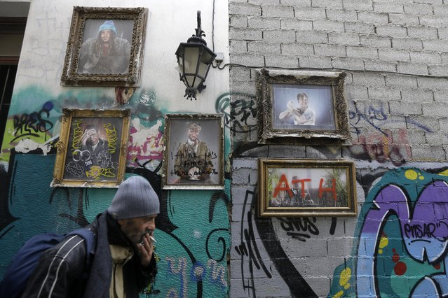 A man smokes a cigarette as he passes a photo installation in Athens, Thursday, February 12, 2015. Talks between Greece and its creditors in the 19-country eurozone broke down Thursday without agreement or even a plan of action on how to move forward on the country's debts and bailout. (Photo by Thanassis Stavrakis/AP Photo)