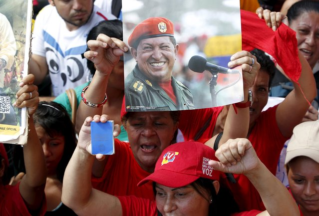 A supporter of Venezuela's President Nicolas Maduro holds up a photograph of Venezuela's late President Hugo Chavez as she gathers with others some streets away from the building housing the National Assembly in Caracas, January 5, 2016. (Photo by Christian Veron/Reuters)