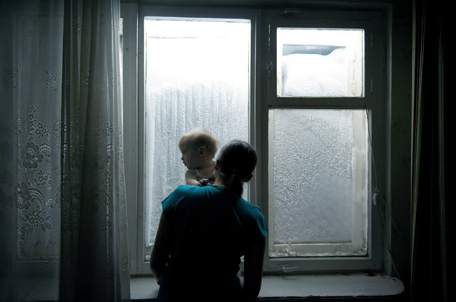 2012. A woman holds her child as they look out at a wall of snow in front of their apartment block. Each year, around 10 tons of snow per inhabitant fall on the city. About 280 days of the year have freezing temperatures. (Photo by Elena Chernyshova)