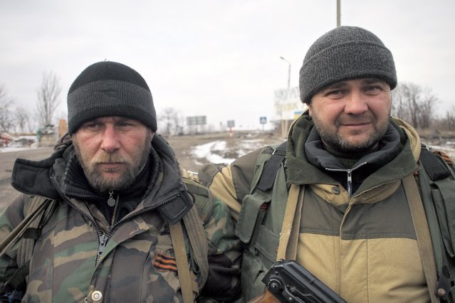 Pro-Russia rebels pose for a photo in Debaltseve, eastern Ukraine on Thursday, February 19, 2015. After weeks of relentless fighting, the embattled Ukrainian rail hub of Debaltseve fell Wednesday to Russia-backed separatists, who hoisted a flag in triumph over the town. The Ukrainian president confirmed that he had ordered troops to pull out and the rebels reported taking hundreds of soldiers captive. (Photo by Peter Leonard/AP Photo)