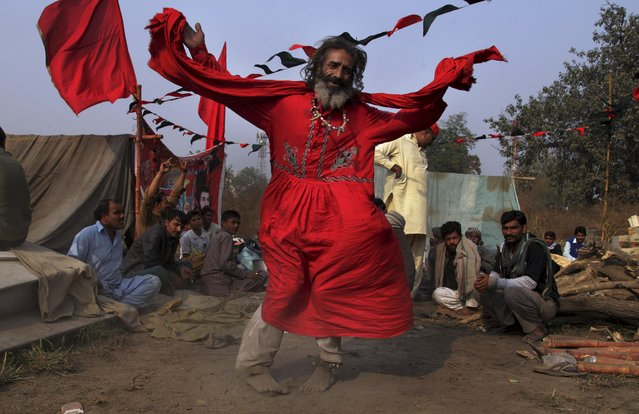 A Pakistani devotee dances to celebrate the three-day annual festival to pay tribute to the famous saint Al-Sheikh Ali Bin Usman Al-Hajveri known as Data Ganjbaksh at outside his shrine in Lahore, Pakistan, Sunday, November 20, 2016. Thousands of people traveled from all over Pakistan to attend the celebrations. (Photo by K.M. Chaudary/AP Photo)