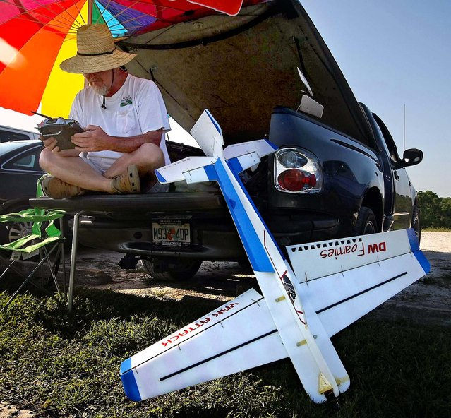 """Phil Petty examines his multiple channel radio control as his plane rests next to him at Phil Wherry Field. """"I have a bunch of hubbies"""", Petty said, """"but in particular these (RC Bush Pilots) are a great bunch of people"""". (Photo by Bill Ingram/The Palm Beach Post)"""