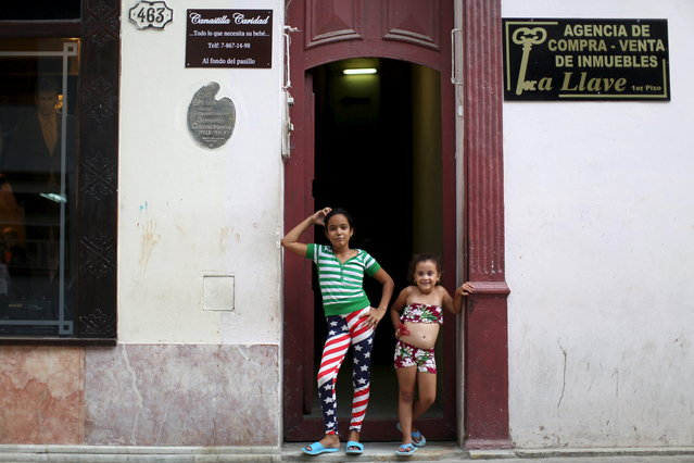 Dianet Tamayo, 10, (L), poses for a photo with Carolina Fernanda Alvarez, 5, at the doorstep of her home in downtown Havana, July 21, 2015. (Photo by Alexandre Meneghini/Reuters)