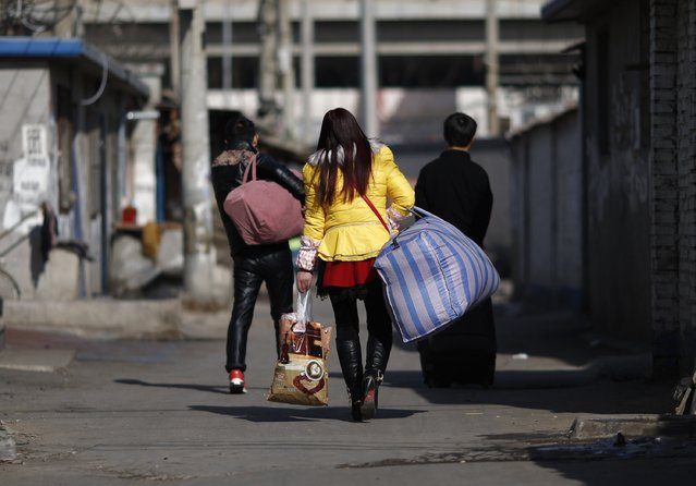 A family of migrant workers carry their belongings towards a bus stop, to wait for a bus that will bring them to a train station, at a migrant workers' village in Beijing February 12, 2015. (Photo by Kim Kyung-Hoon/Reuters)