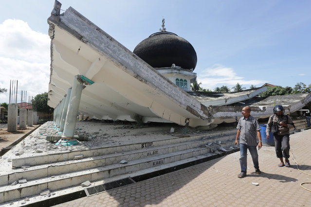 People walk near a collapsed mosque following an earthquake in Meuredu, Pidie Jaya in the northern province of Aceh, Indonesia December 7, 2016. (Photo by Irwansyah Putra/Reuters/Antara Foto)
