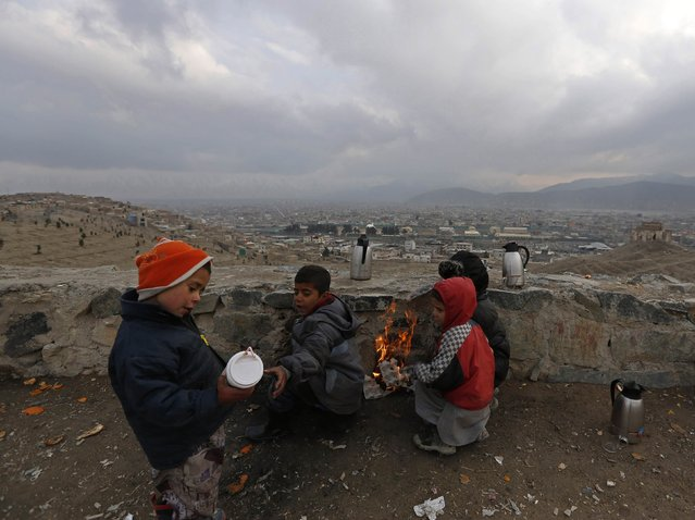 Afghan children, who are selling tea, warm themselves by a fire on a cold day in Kabul, February 2, 2015. A tea vendor earns $1 on average a day. (Photo by Mohammad Ismail/Reuters)