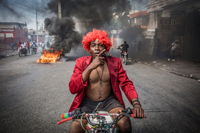 Demonstrators march in Port-au-Prince on February 14, 2021, to protest against the government of President Jovenel Moise. Several thousand people demonstrated Sunday in the Haitian capital Port-au-Prince, saying the government was trying to establish a new dictatorship and denouncing international support for President Jovenel Moise. The protests were mostly peaceful, although a few clashes broke out between some demonstrators and police, who fired tear gas and rubber bullets. (Photo by Valerie Baeriswyl/AFP Photo)