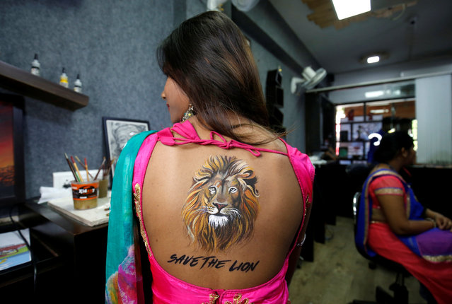 A woman poses after she got an image of a lion tattooed on her back as part of awareness campaign to save Asiatic lions and in preparations for the upcoming Navratri festival in Ahmedabad, India, October 5, 2018. (Photo by Amit Dave/Reuters)