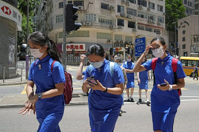 Students wearing face masks to prevent the spread of coronavirus, walk across a street in Hong Kong, Thursday, June 10, 2021. Government officials said Thursday that they will expand the vaccination drive to about 240,000 children from 12 to 15 years old starting Friday, joining other countries such as Singapore and the U.S. that have started vaccinating children. (Photo by Kin Cheung/AP Photo)