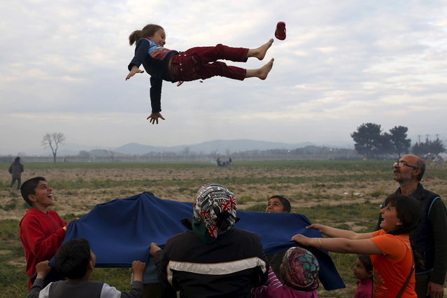 Children play at a makeshift camp for migrants and refugees at the Greek-Macedonian border near the village of Idomeni, Greece, March 29, 2016. (Photo by Marko Djurica/Reuters)