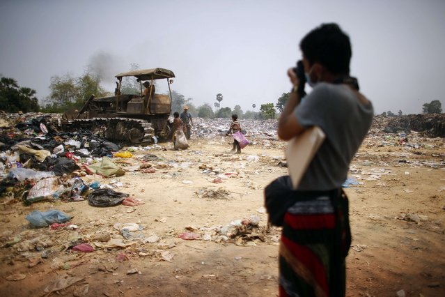 A Japanese tourist takes pictures of people working at a landfill dumpsite outside Siem Reap March 19, 2015. The tourist, who was visiting the famous Angkor Wat tourist attraction nearby, came alone to see people working at the dumpsite. (Photo by Athit Perawongmetha/Reuters)