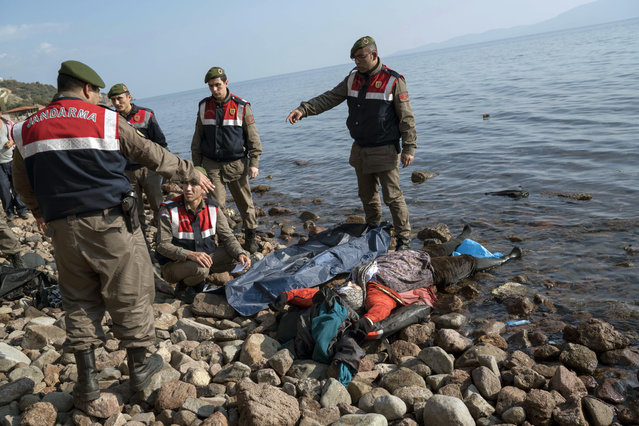 Turkish paramilitary police officers collect the dead body of a migrant from the beach near the Aegean town of Ayvacik, Canakkale, Turkey, Saturday, January 30, 2016. (Photo by Halit Onur Sandal/AP Photo)