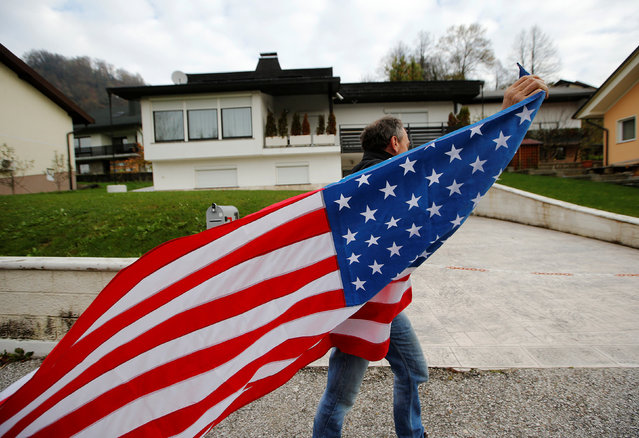 SLOVENIA: A man carrying the U.S. flag is seen in front of Melania Trump parents' house during the U.S. presidential election in Melania Trump's hometown of Sevnica, Slovenia November 9, 2016. (Photo by Srdjan Zivulovic/Reuters)