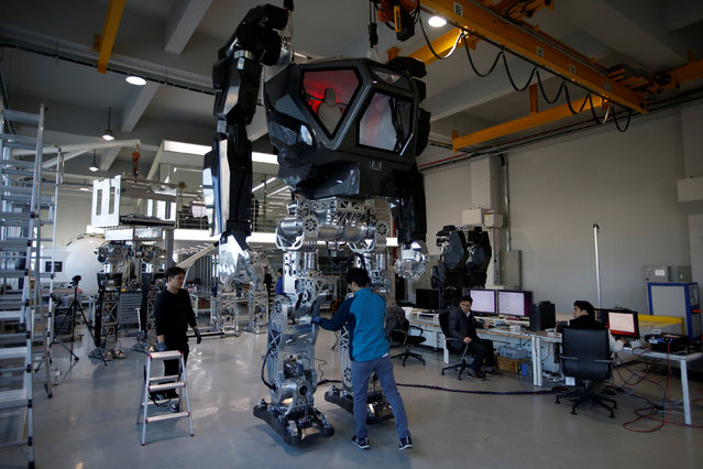 """Employees check a manned biped walking robot """"METHOD-2"""" during a demonstration in Gunpo, South Korea, December 27, 2016. It stands 13-feet (3,96 m) tall, weighs 1.3 tons and wields a pair of 286-pound (129,73 kg), motion-tracking metal arms. """"Our robot is the world's first manned bipedal robot and is built to work in extreme hazardous areas where humans cannot go (unprotected)"""", Hankook Mirae Technology company chairman, Yang Jin-Ho, said in a prepared statement. The company has spent upwards of $200 million since 2014 to develop the mech with the help of Hollywood SFX designer, Vitaly Bulgarov, whose credits include Transformers, Robocop and Terminator. The Method-2 itself likely won't be employed in the field anytime soon. Instead, the giant machine will serve as a testbed for emerging mech technologies. Future iterations, however, could find use in everything from construction and cargo loading to military and SAR operations. (Photo by Kim Hong-Ji/Reuters)"""