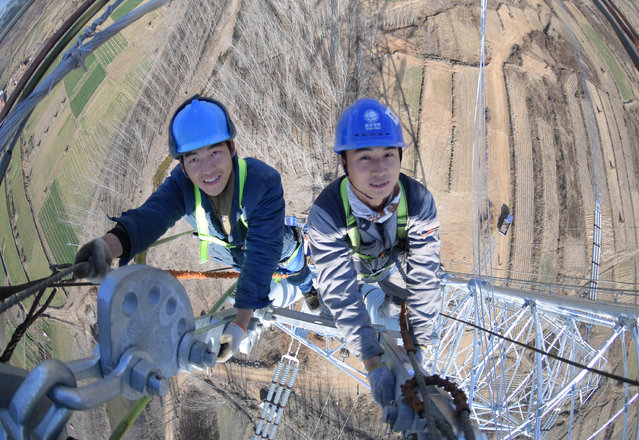 Workers on the Shandong to Hebei Uhv looped power lines network project in Rizhao, Shandong, China on November 22, 2018. (Photo by TPG/TPG via ZUMA Press/Rex Features/Shutterstock)