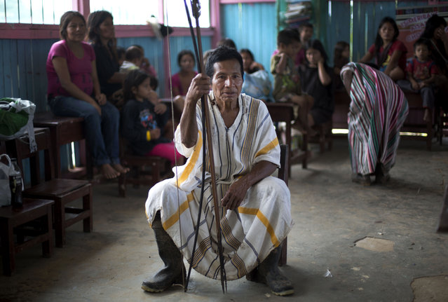 In this March 16, 2015 photo, Ashaninka Indian Guillermo Arevalo holds onto to his bow and arrow during a community meeting to discuss land titles and education, in the hamlet of Saweto, Peru. Saweto holds weekly meetings to discuss local issues, where all adults have the right to address the gathering. (Photo by Martin Mejia/AP Photo)