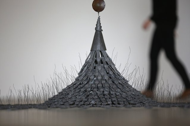"""A gallery staff member walks past Fleeting Monument (1985)  by artist Cornelia Parker, one of the works on display at Yorkshire Sculpture Parks Longside Gallery as part of the """"Making It: Sculpture in Britain 1977-1986"""" exhibition on March 27, 2015 in Barnsley, England. (Photo by Christopher Furlong/Getty Images)"""