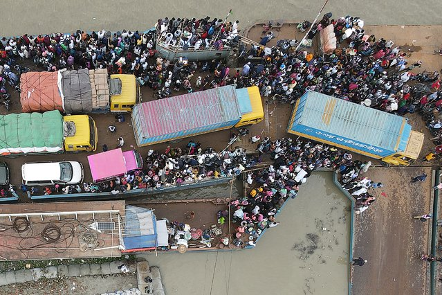 In this aerial photo taken on June 27, 2021, people board a ferry as authorities ordered a new lockdown to contain the spread of the Covid-19 coronavirus, in Munshiganj. (Photo by Munir Uz Zaman/AFP Photo)