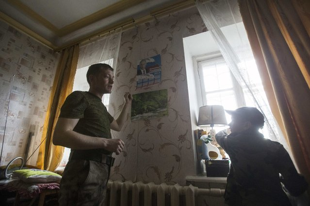 Valery, 30, a member of the People's Militia of Crimea, talks to his son Kirill inside their house, next to a calendar with a portrait of Russian President Vladimir Putin on the wall, on the first anniversary of the Crimean referendum to secede from Ukraine and join Russia, in Simferopol, March 16, 2015. (Photo by Maxim Shemetov/Reuters)