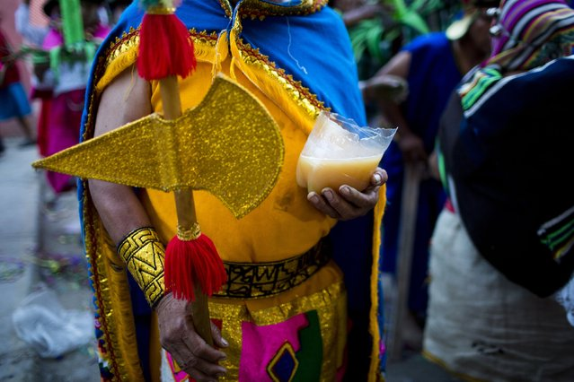 In this Sunday, March 29, 2015 photo, a Vilcashuaman dance troupe member, dressed as an Inca leader, holds the bottom half of a plastic soda bottle filled with chicha, a popular drink made with fermented corn, as he waits to perform in the Vencedores de Ayacucho dance festival, in the Acho bullring in Lima, Peru. (Photo by Rodrigo Abd/AP Photo)