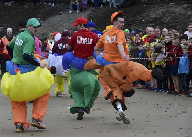 Competitors run backwards during a fancy dress race before the New Year's Day swim at Saundersfoot in Wales, Britain, January 1, 2017. (Photo by Rebecca Naden/Reuters)