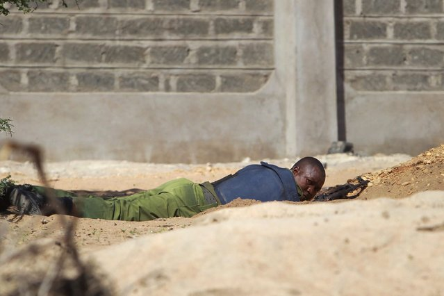 A Kenyan soldier takes cover as shots are fired in front of Garissa University in Garissa town, located near the border with Somalia, some 370km northeast of the capital Nairobi, Kenya, 02 April 2015. At least 15 people have been killed and some 60 were injured in an attack carried out by Somalia's Islamist militant group al-Shabab, according to local media reports. (Photo by Dai Kurokawa/EPA)