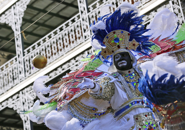 A member of the Zulu Social Aid and Pleasure Club throws a coconut during Mardi Gras day on February 9, 2016 in New Orleans, Louisiana. (Photo by Jonathan Bachman/Getty Images)