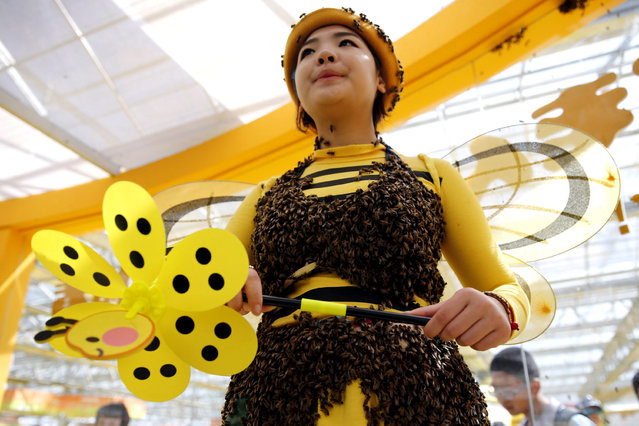 A performer wears a hat and outfit covered with bees at an exhibition hall about beekeeping during the Beijing Agricultural Carnival April 3, 2015. (Photo by Kim Kyung-Hoon/Reuters)