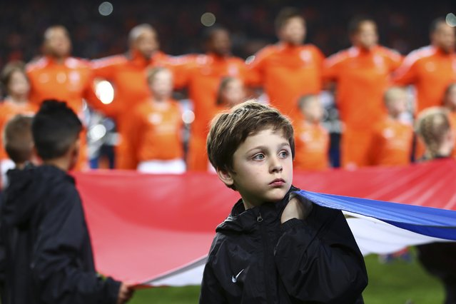 A boy holds the national flag as players of the Netherlands, rear, line up prior to the Euro 2016 group A qualifying soccer match between the Netherlands and Turkey at Arena stadium in Amsterdam, Netherlands, Saturday, March 28, 2015. (Photo by Peter Dejong/AP Photo)