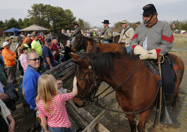 Civil War re-enactor Steve Riggs, of Charleston S.C., with the 2nd Virginia Cavalry, lets visitors pet his horse, Jackson, before a re-enactment of the Battle of Appomattox Station, Wednesday, April 8, 2015, as part of the 150th anniversary of the surrender of the Army of Northern Virginia to Union forces at Appomattox Court House, in Appomattox, Va. (Photo by Steve Helber/AP Photo)