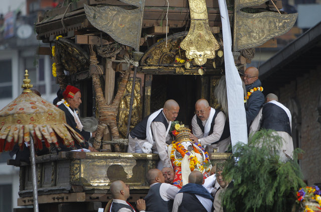 Priests carry the idol of Seto Machindranath to place inside the chariot which will then be pulled by devotees during the Seto Machindranath Chariot festival in Kathmandu, Nepal, Friday, March 27, 2015. (Photo by Niranjan Shrestha/AP Photo)