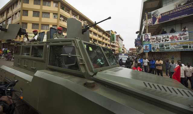 Ugandan soldiers ride in an armored personnel carrier equipped with heavy-calibre weapons as they patrol past opposition supporters, shortly after the election result was announced, in Kampala, Uganda, Saturday, February 20, 2016. (Photo by Ben Curtis/AP Photo)